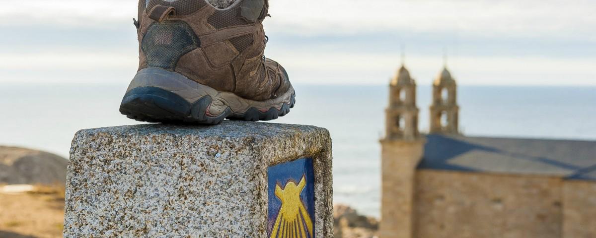 Santuario de Nosa Señora da Barca en Muxía e fito de pedra coa sinalización do Camiño de Santiago